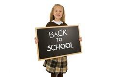 Skolflicka som ler det lyckliga innehavet och den lilla svart tavla för visning med text tillbaka till skolan Royaltyfri Foto