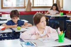 Skolflicka som ser bort, medan dra i klassrum Arkivbild