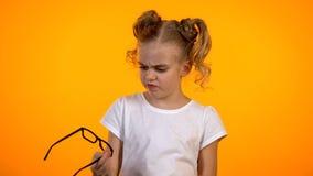 Skolflicka som ser exponeringsglas med avsmak, synförmågakorrigering, oftalmologi arkivbild