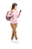 Skolflicka som ser hennes mobiltelefon royaltyfria bilder