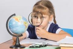 Skolflicka som ser jordklotet till och med ett förstoringsglas Arkivbilder