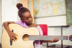 Skolflicka som spelar gitarren i klassrum Royaltyfria Foton