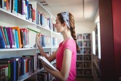 Skolflicka som väljer boken från bokhylla i arkiv Arkivfoto