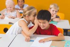 Skolflicka som viskar in i hennes öra för vän s i klassrum Fotografering för Bildbyråer