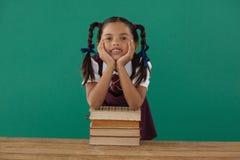 Skolflickabenägenhet på bokbunt mot den svart tavlan i klassrum Royaltyfria Bilder