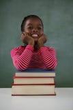 Skolflickabenägenhet på bokbunt mot den svart tavlan i klassrum Royaltyfri Fotografi