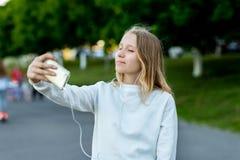 Skolflickaflickan i sommar på parkerar i gata I hans handhåll en smartphone som tar bilder av honom på telefonen arkivbilder