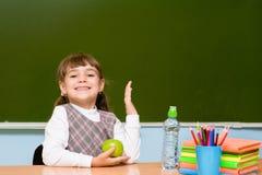 Skolflickagrundskola som lyfter händer som vet svaret till frågan royaltyfri bild