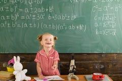 Skolflickaleende på den svart tavlan för klassrum Den lyckliga skolflickan har kurs i grundskola för barn mellan 5 och 11 år arkivbild