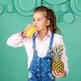 Skolflickan dricker ananasfruktsaft för frukostfyrkant Th fotografering för bildbyråer