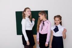 Skolflickan för tre flickor står på svart tavla med kurs arkivfoto