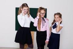 Skolflickan för tre flickor står på svart tavla med kurs royaltyfri fotografi