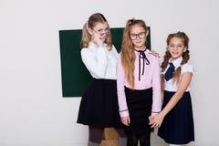 Skolflickan för tre flickor står på svart tavla med kurs fotografering för bildbyråer