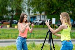 Skolflickan för två flickor ska anteckna videoen på kameran känslomässigt med shower för handgester Använd en tripod för att skri royaltyfria foton