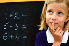 Skolflickan grubblar lösa ett matematiskt problem Royaltyfria Bilder