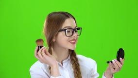 Skolflickan i exponeringsglas som pudrar hennes näsa med en borste, ser i spegeln grön skärm stock video