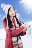 Skolflickan i vinterkläder skriver på skrivplattan Royaltyfri Bild