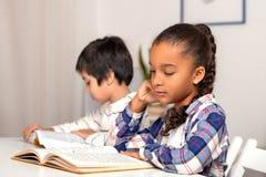 Skolflickan och skolpojken som inomhus placerar p? tabellen och g?r deras l?xa arkivbilder