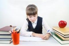 Skolflickan sitter på tabellen och skriver bland böcker och äpplet Royaltyfria Foton
