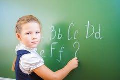 Skolflickan skrev i krita på svart tavla och undervisar engelskt språk royaltyfri foto