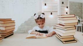 Skolflickasammanträde på en tabell och en läsning en bok arkivfilmer