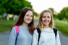 Skolflickatonåring för två flickor, i sommar efter skola i natur Att att posera på kamera Sinnesrörelser av glädje och nöje _ arkivfoto