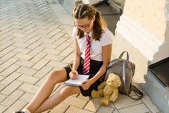 Skolflickatonåringen skriver i en anteckningsbok Dagbokflickor, hemligheter, första förälskelse fotografering för bildbyråer