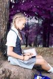 Skolflickatonåringen som läser en bok i, parkerar nära ett träd arkivbilder