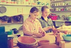 Skolflickor som arbetar med lera Arkivfoto