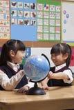 Skolflickor som ser ett jordklot i klassrumet Arkivbild