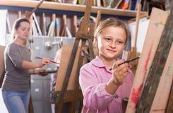 Skolflickor som utbildar arbetsamt deras målningexpertis under cla royaltyfria bilder