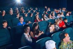 Skolkamrater som håller ögonen på film i bion Arkivbild