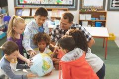 Skollärare som påverkar varandra med hans elever över ett jordjordklot som sätter på en tabell i klassrum på schoen royaltyfri bild