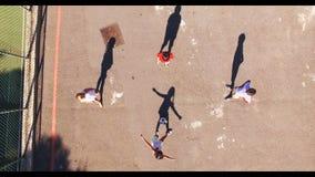 Skolpojkar som spelar fotboll i lekplats arkivfilmer