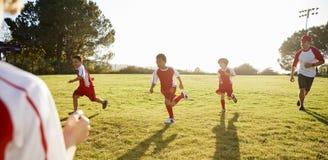 Skolpojkar som spelar fotboll med deras lagledare arkivfoto