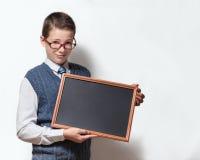 Skolpojke i exponeringsglas med med den tomma svart tavlan Royaltyfri Fotografi