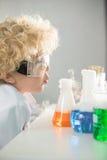 Skolpojke i skyddande skyddsglasögon som ser flaskor och rör Arkivbilder