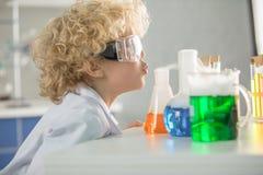 Skolpojke i skyddande skyddsglasögon som ser flaskor och rör Arkivfoton