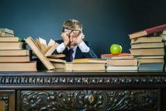 Skolpojke i spänning eller fördjupning på skolaklassrumet Arkivbilder