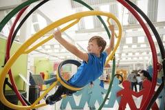 Skolpojke i vetenskapsmitt genom att använda det mänskliga gyroskopet, sidosikt royaltyfri bild