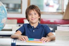 Skolpojke med böcker och jordklotet på skrivbordet Arkivbild