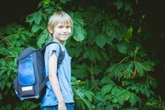 Skolpojke med en ryggsäck som går till skolan Utbildning tillbaka till skolan, folkbegrepp Royaltyfri Foto