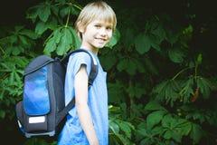 Skolpojke med en ryggsäck som går till skolan Utbildning tillbaka till skolan, folkbegrepp Royaltyfri Fotografi
