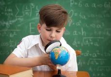 Skolpojke med jordklotet och loupen Arkivfoto