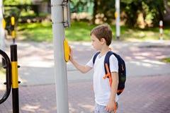 Skolpojke med ryggsäcken som trycker på en knapp på trafik Arkivbild