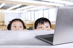Skolpojke och skolflicka som kikar bärbara datorn i klassrum royaltyfri fotografi