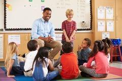Skolpojke på framdelen av elementär grupp med läraren arkivfoton