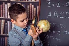 Skolpojke som använder förstoringsglaset som ser jordklotet Royaltyfri Fotografi