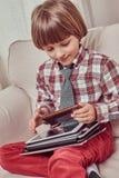 Skolpojke som bär en rutig skjorta som hemma sitter på en soffa med uppsättningen av minnestavlor royaltyfria bilder