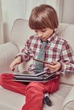 Skolpojke som bär en rutig skjorta som hemma sitter på en soffa med uppsättningen av minnestavlor royaltyfria foton